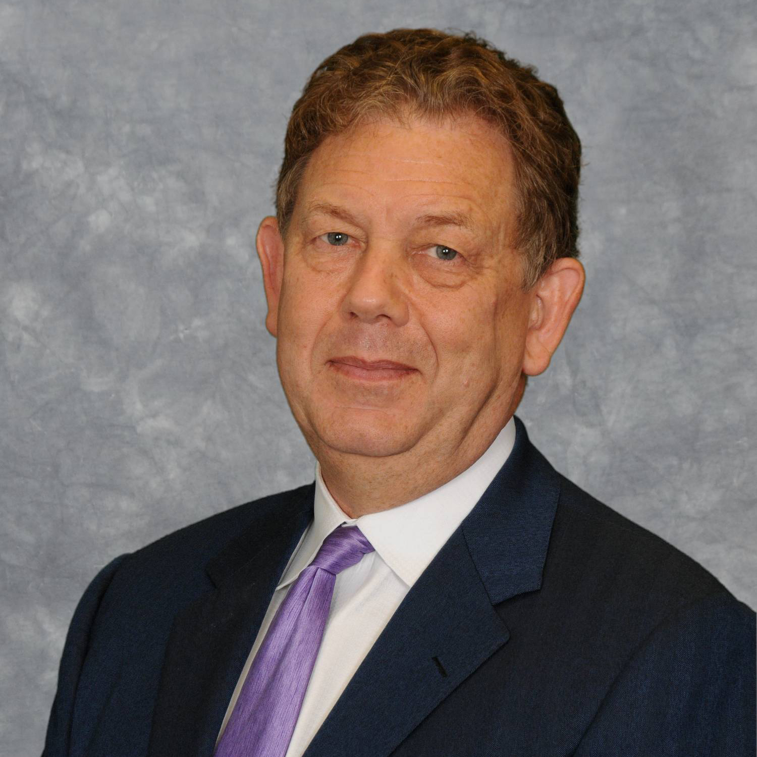 headshot of Dr. Alan Lumsden wearing a black suit and purple tie